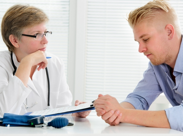 Doctor talking to her male patient in her office