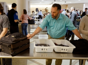 Airline passengers wait in line before passing through a TSA checkpoint at LAX