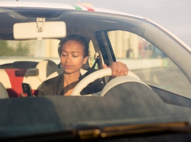 Young woman texting in car