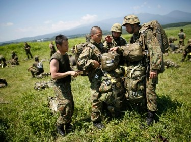 Japanese Ground Self-Defense Force soldiers carry parachutes for drop training during a military drill west of Tokyo, July 8, 2013