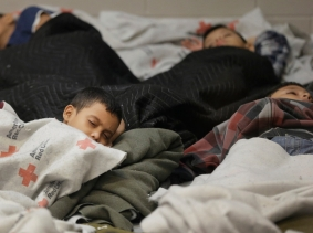 Detainees sleep in a holding cell at a U.S. Customs and Border Protection processing facility, June 18, 2014, photo by Eric Gay/Pool/Reuters