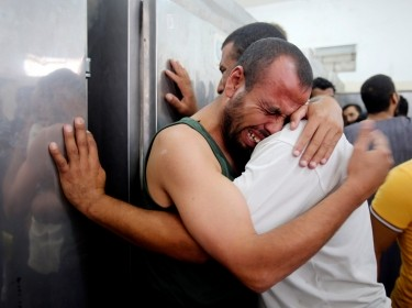 Palestinians mourn their relatives, whom medics say were killed by Israeli shelling, at a hosp