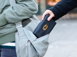 Pickpocket stealing a woman's wallet