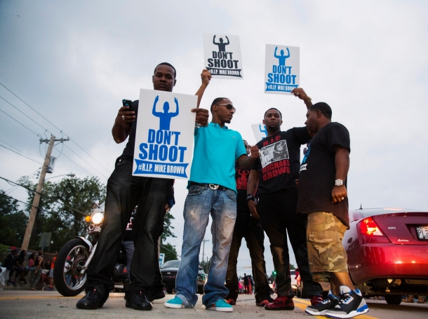 Demonstrators gesture and chant as they continue to react to the shooting of Michael Brown in Ferguson, Missouri August 17, 2014