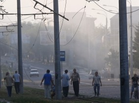People walk along the street soon after, what locals say, was recent shelling by Ukrainian forces, in Donetsk on August 20, 2014