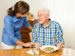 An elderly man getting served a meal by his daughter