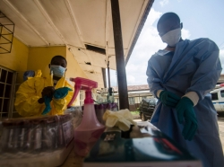 Medical staff put on protective gear before taking a sample from a suspected Ebola patient in Kenema, Sierra Leone, July 10, 2014