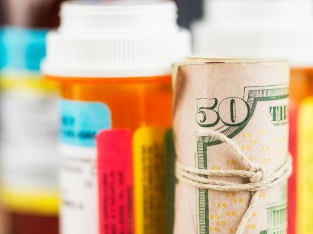 U.S. currency wrapped around prescription bottle