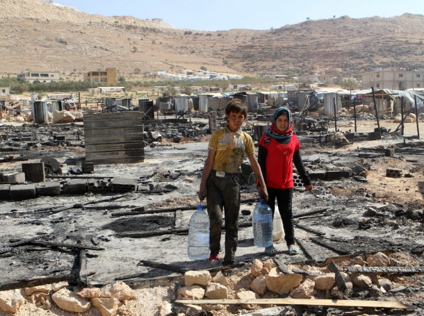 Syrian refugees walk amid damage and the remains of tents that were burnt in the fighting between Lebanese army soldiers and Islamist militants in the Sunni Muslim border town of Arsal, August 9, 2014