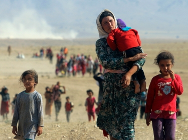 Displaced people from the minority Yazidi sect, fleeing violence from the Islamic State, walk towards the Syrian border, on the outskirts of Sinjar mountain, August 11, 2014