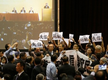 Pro-democracy lawmakers protest as Li Fei (on screen), deputy general secretary of the National People's Congress standing committee, speaks during a briefing session in Hong Kong Sept. 1, 2014