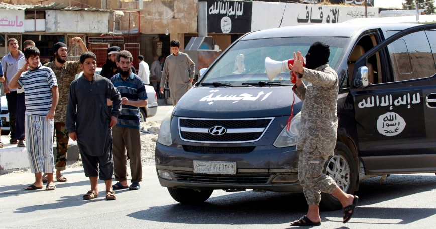 An Islamic State militant uses a loud-hailer to announce to residents of Tabqa city that Tabqa air base has fallen to Islamic State militants, August 24, 2014