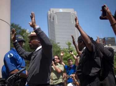 Activists, demanding justice for the shooting death of teen Michael Brown, raise their hands as they are blocked by police from entering the courthouse in St. Louis, Missouri