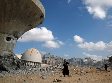 Palestinians walk past a mosque and water tower damaged by Israeli air strikes and shelling in Khuzaa, in the southern Gaza Strip