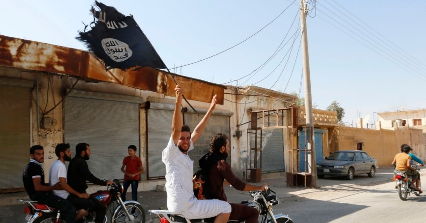 A resident of Tabqa city on a motorcycle waves an Islamist flag in celebration after Islamic State militants took over Tabqa air base, August 24, 2014