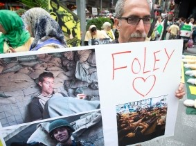 A man holds up a sign in memory of U.S. journalist James Foley during a protest against the Assad regime in Syria in New York City, August 22, 2014