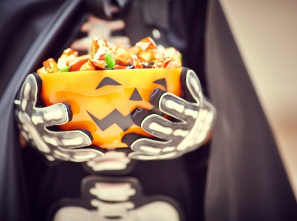 Child in skeleton costume with a jack-o-lantern basket of candy