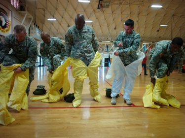 U.S. Army soldiers, earmarked for the fight against Ebola, put on protective suits during training before their deployment to West Africa, October 9, 2014