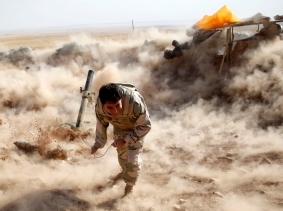 A Kurdish Peshmerga fighter launches mortar shells towards Zummar, controlled by the Islamic State, near Mosul, September 15, 2014