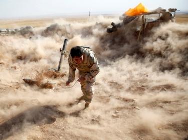 A Kurdish Peshmerga fighter launches mortar shells towards Zummar, controlled by the Islamic State, near Mosul, September 15, 2014