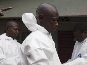 A burial team wearing protective clothing prepares to enter the home a person suspected of having died from Ebola in Freetown, Sierra Leone, September 28, 2014, photo by Christopher Black/WHO/Handout via Reuters