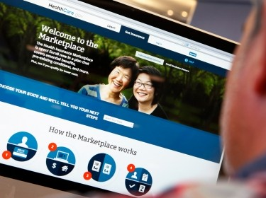 A man looks over the ACA signup page on HealthCare.gov, October 2, 2013