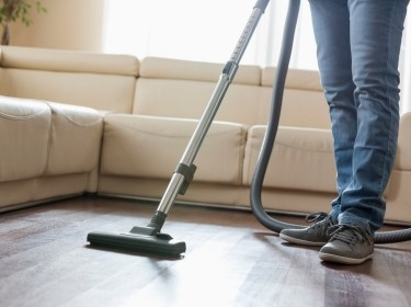 A man cleaning hardwood floor with vacuum cleaner