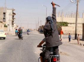A man holds up a knife as he rides on the back of a motorcycle in celebration after Islamic State militants took over Tabqa air base, in Raqqa, Syria, August 24, 2014