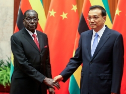 Zimbabwe's President Robert Mugabe and China's Premier Li Keqiang in Beijing on August 26, 2014. Officials say Mugabe is seeking funds to rebuild decaying roads, rail and power facilities, and to help mechanise Zimbabwe's agriculture.