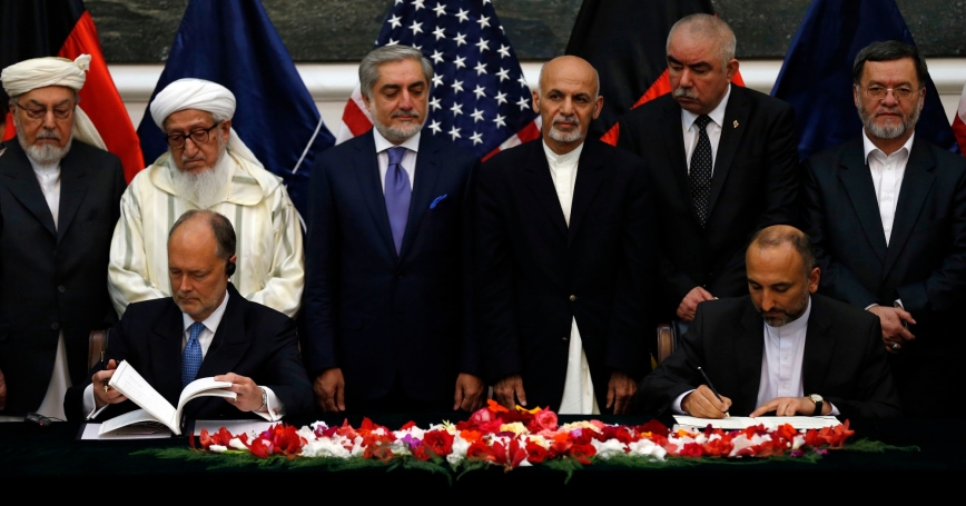 Afghan national security adviser Hanif Atmar (front R) and U.S. Ambassador James Cunningham sign the bilateral security agreement as Afghan President Ashraf Ghani Ahmadzai (back 3rd R) and Chief Executive Abdullah Abdullah (back 3rd L) look on, in Kabul, September 30, 2014