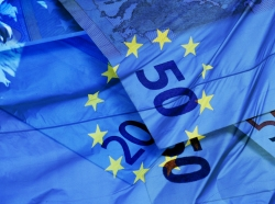 A European flag superimposed over euro banknotes