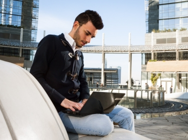 Young man working at computer outside