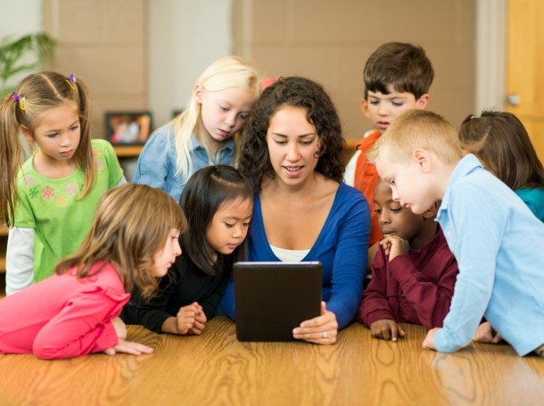 Preschoolers in a classroom looking at a tablet with their teacher