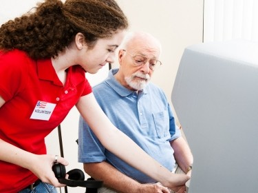 A teenage election volunteer helping a senior man use a touch screen
