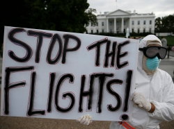 A protestor demonstrates in favor of a travel ban to stop the spread of Ebola, in front of the White House, October 16, 2014