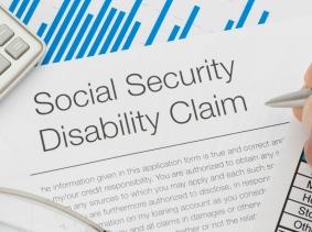 Social Security Disability claim form, pen, calculator
