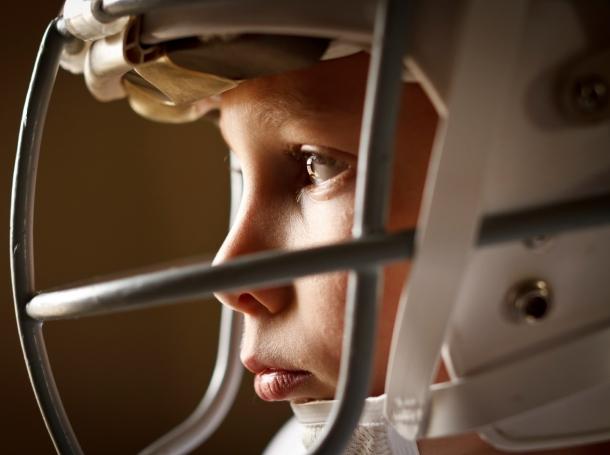 A boy wearing a football helmet