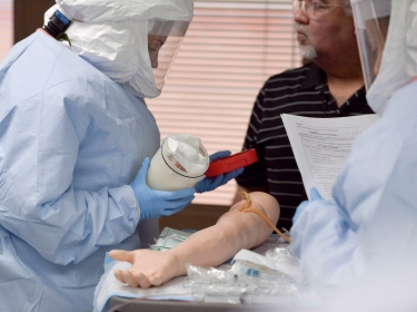Participants practice a medical procedure on a dummy arm during training for the Ebola response team at Fort Sam Houston in San Antonio, Texas, October 24, 2014