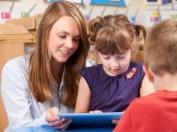 A teacher helps a girl use a digital tablet