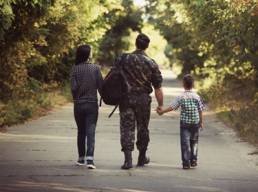 Military family walking on a path through the woods