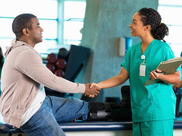 A physical therapist greeting a patient in a hospital rehab gym