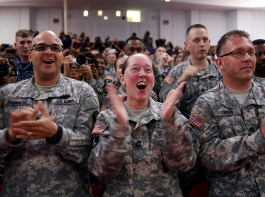 U.S. Army soldiers cheer as U.S. President Barack Obama signs H.R. 3230, the Veteran's Access to Care through Choice, Accountability and Transparency Act of 2014