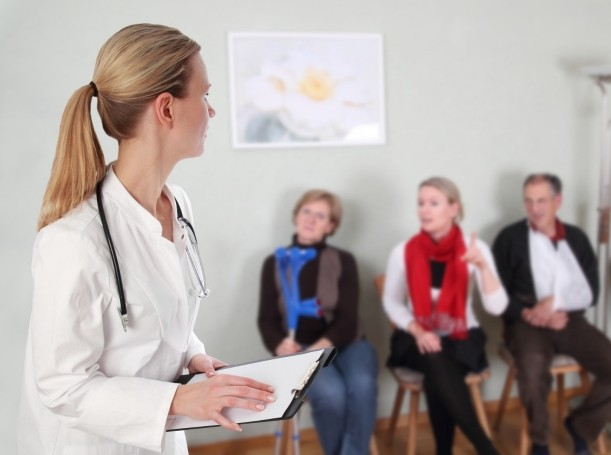 Doctor with a clipboard and patients in a waiting room