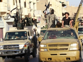 Militant Islamist fighters parade along the streets of Syria's northern Raqqa province