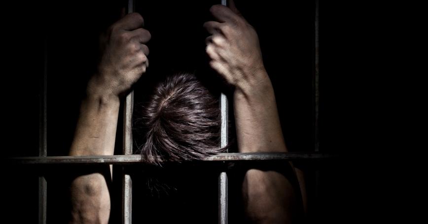 A prisoner, behind bars
