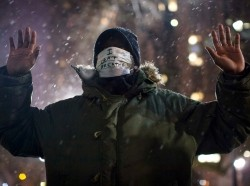 A man holding a 'Hands Up, Don't Shoot' pose and wearing an 'I Can't Breathe' mask outside City Hall, New York City, December 10, 2014