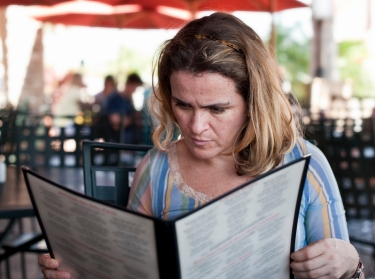 A woman reading a menu at a restaurant