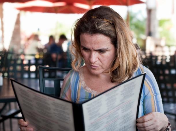 A woman reading a menu at a restaurant