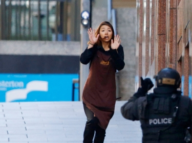 A hostage runs toward a police officer outside Lindt cafe, wher