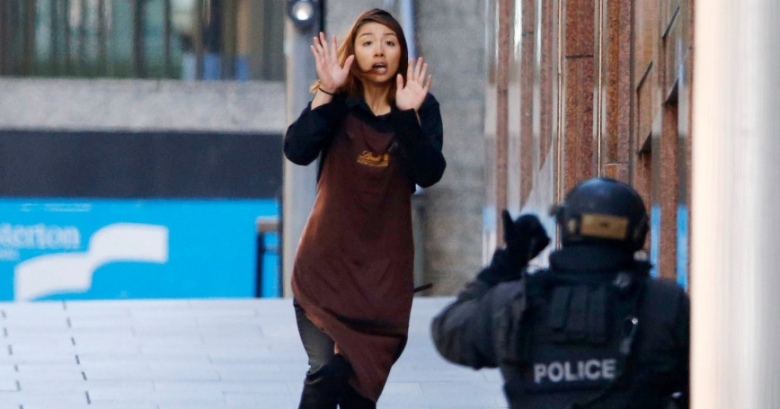 A hostage runs toward a police officer outside Lindt cafe, where other hostages are being held, in Martin Place, Sydney, December 15, 2014